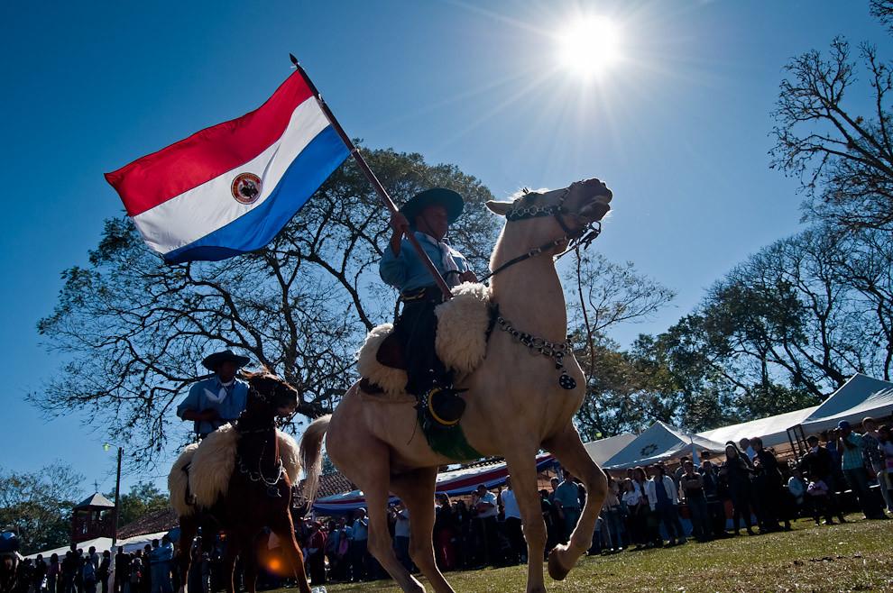 Un jinete portador de la bandera paraguaya marcha hacia el área central de la Plaza San Miguel, a pocos minutos del comienzo de la jineteada, que consiste en demostración de talento y doma. Eventos que se llevaron a cabo el sábado 11 por la tarde y el domingo 12 de junio por la mañana. (Elton Núñez, San Miguel - Paraguay)