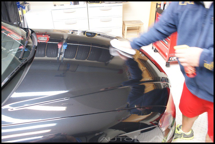 gently wiping Dodo Juice Red Mist onto a polished clear-coat finish