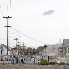 Man Walking, Blimp (metroblossom) Tags: california man walking traintracks snoopy bayarea blimp metlife alameda residential dirigible img55504c