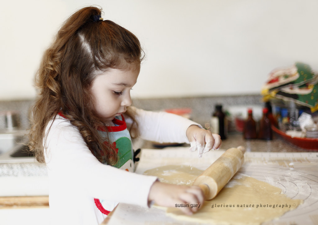 Cute Toddler Girl Sprinkling Flour on Cookie Dough