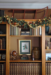 Christmas-bookcase (kizilod2) Tags: christmas red brown holiday gold display bookshelf garland decorating ribbon bookcase sled decor shelves