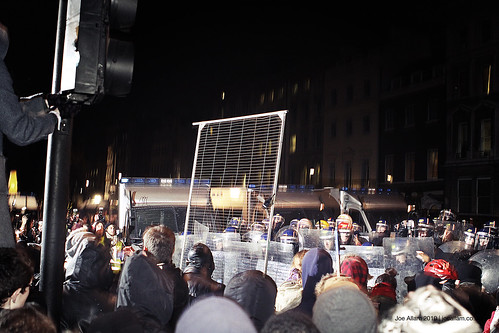 Protesters Rioting With a Fence
