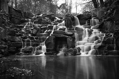 Man Made Cascade, Virginia Water (flatworldsedge) Tags: longexposure england white black blur reflection wet water forest virginia waterfall rocks force thomas stones trails surrey spray manmade cascade sandby explored improvisedtripod yahoo:yourpictures=blackandwhite yahoo:yourpictures=water yahoo:yourpictures=waterv2
