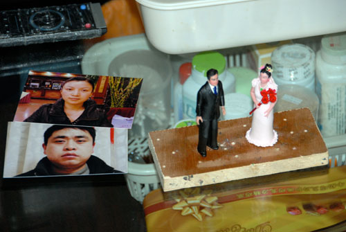 Tiny dough figures of bride and groom alongside their photographs