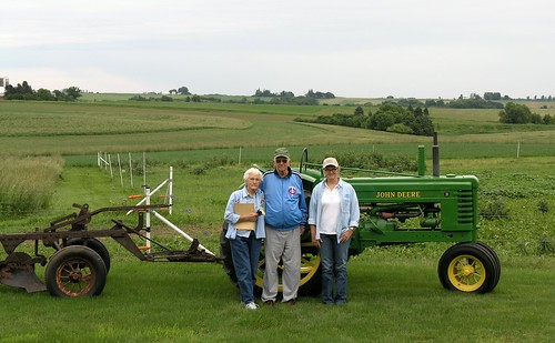 Caryl Radatz with her parents, Charles and Coralyn Radatz, in front of John Deere tractor used to install contour strips in 1943.