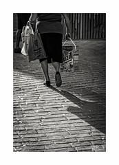 La compra (ngel mateo) Tags: ngelmartnmateo ngelmateo sombra mujer compra empedrado detergente luzil bolsa pan cobbles detergent shadow woman buys bread bag