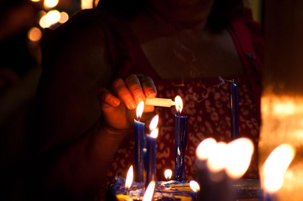 Una Señora enciende sus velas frente a la Capilla lateral de la Basílica de Caacupé, para elevar sus oraciones a la Virgen durante la Vigilia nocturna del 7 de Diciembre. (Elton Núñez - Caacupé, Paraguay)