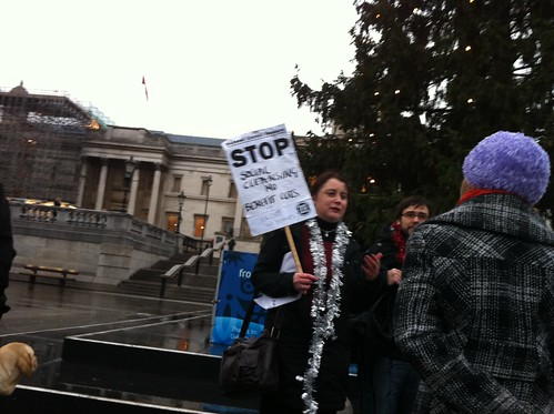 A woman standing under the tree holding up a sign saying 'stop social cleansing and benefit cuts'