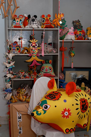 Brightly colored cloth animals of various sizes displayed in a shop