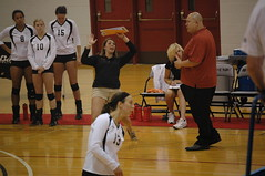 The assistant coach went wild on this play. (kennethkonica) Tags: red usa white black men sports teams women shoes shiny doors sitting legs chairs indianapolis bald indiana excited shorts uniforms players gym sits kneepads clipboards uindy tusculumvolleyball
