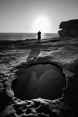 Couple at sunset - Dwejra, Malta - Black and white street photography (Giuseppe Milo (www.pixael.com)) Tags: layered calm peaceful nature water beauty sea summer contrast ocean love photography black depth white photo tranquil prints stone sunset malta bay european azurewindow dwejra faceless shore coast view rocks wallart sun europe photograph scenic beautiful natural fineart canvas print blackandwhite seascape sky monochrome bw onsale