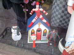 A close up of the church montage. A small model of a quaint country church, completed with steeple. A snowman is placed beside the church. An action figure of a superhero is on the other side. Straddling the church is a female superhero. A Santa Pez dispenser stands outside the door of the church.