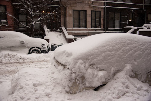 Car buried under snow in NYC with a subway sign