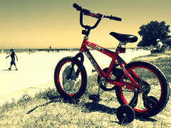 One Day When I Grow Up (Flint Foto Factory) Tags: city red summer urban bw chicago tower beach boys grass bike bicycle kids hope freedom pier sand aspiration july lifeguard lakemichigan tires hollywood dreams childrens connected wish wonderment gazing sheridan belong edgewater trainingwheels handlebars longing ardmore wistful 2010 wishful realization feelsgood kathyosterman