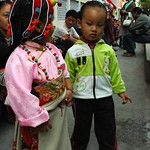 Modeling her Tibetan outfit - a silk decorated chuba, head-dress, coral pearl & turquoise necklace, fancy chuba, pink blouse, with her reflective friend in a green, white, and black outfit, Tharlam Monastery Courtyard, Boudha, Kathmandu, Nepal thumbnail