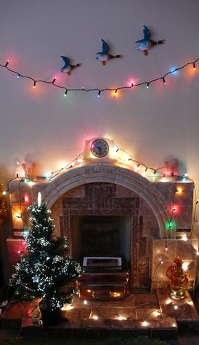 Christmas lights around 1930s tiled fireplace