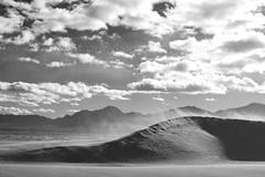 The Blowing Dune (one_vision_photo) Tags: blackandwhite mountains clouds blackwhite deathvalley sanddune sanddunes desertlandscape sculpting blowingsand strongwinds howlingwinds