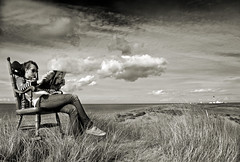 Relaxing the Isle of Man way. (IMAGES FROM MAN.) Tags: sea summer sky blackandwhite bw sun lighthouse nature water sepia lady clouds magazine relax landscape reading coast seaside sand nikon raw mood moody sunny monotone d200 rockingchair ayres sandunes tranquil cloudscape atmospheric isleofman manx cloudscapes pointofayre 18200vr raycollister