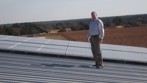 Johnny Smith, Area Director, views the recently installed photovoltaic cells on the roof of the Red Caboose Winery main building.
