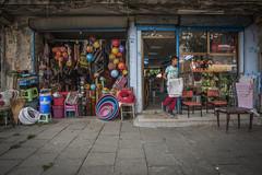 A Barber Apprentice & colorful plastic footballs (Mustafa Karaoglu) Tags: adana turkey barber apprentice child work environmentalportrait