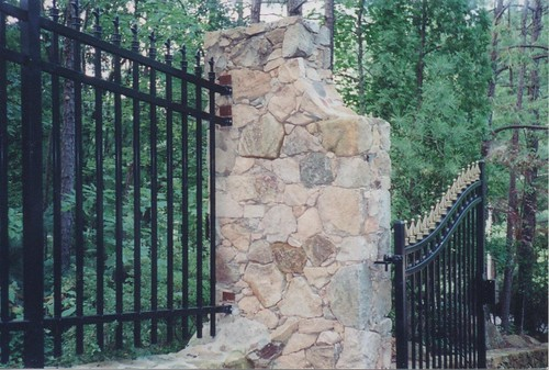curved stone column where fence meets stone entrance sign and security gate