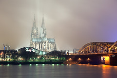Cologne's Biggest, Baddest and Boldest (Allard One) Tags: city longexposure nightphotography bridge panorama mist misty fog skyline architecture night river germany deutschland nikon cathedral dom january cologne panoramic le brug portfolio riverbank rhine rhein koln nordrheinwestfalen stad rijn lightbeams architectuur januari gettyimages newyearsday happynewyear duitsland kathedraal keulen rivier spoorbrug northrhinewestphalia 2011 jaarwisseling oever hohenzollernbrcke kennedyufer turnoftheyear nieuwjaarsdag hohedomkirchestpeterundmaria d700 nikond700 nikkor2470mmf28 nikkor2470 nikon2470 nikonfx allardone allard1 noordrijnwestfalen wateflowing allardschagercom