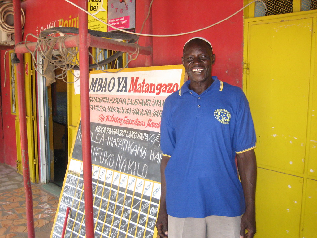 Farmer Hamis Birika in front of a market price information board at the KIRSEC telecentre