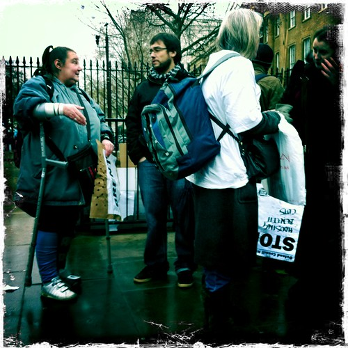 2 people conversing in the background while in the foreground a woman is holding upside down a sign which says 'stop housing benefit cuts'