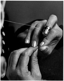 Close-up of a woman's hands threading a needle, wearing a thimble