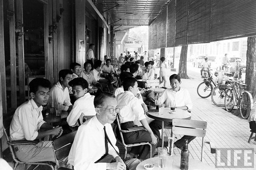 Men drinking at a sidewalk cafe in Saigon circa 1961