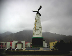 tashkurgan - eagle of the pamir (Xuan Che) Tags: 2005 china street city travel summer sculpture mountain west bronze town highway eagle cloudy border august xinjiang silkroad karakoram column tajik centralasia canonixus400 pamir tashkurgan highplateau