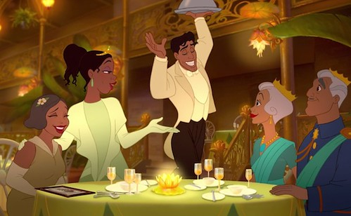Image description: Tiana's mother and Naveen's parents sitting at a table in a restaurant. Tiana has a hand on her mother's shoulder, while gesturing at Naveen with the other. Naveen has one hand in the air and the other holding a covered platter.