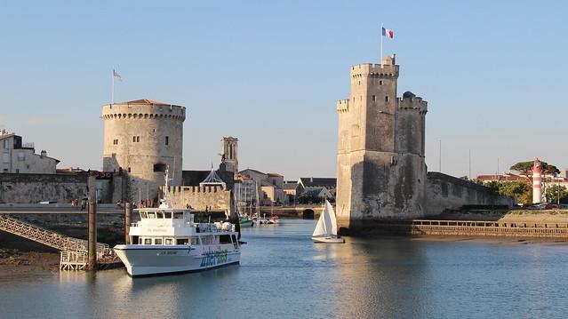 Lentrée du port, avec à gauche la tour de la Chaîne (XIVe siècle), à droite la tour Saint-Nicolas (XIVe siècle) et au fond le clocher de léglise Saint-Sauveur (XIIe siècle)