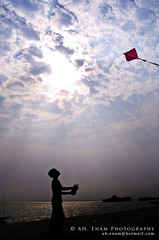 Feel the freedom (Anwar Hussain Enam) Tags: boy red sky cloud kite playing color sunshine silhouette kid ray 2010 2011
