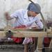 Girl spins freshly extracted silk - Hotan, Xinjiang