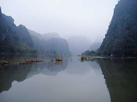 The trail back to Ninh Binh passes by a water reservoir flanked by limestone mountains
