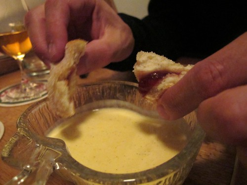 "A pot of custard or as the French say ""creme Anglaise"" with doughnuts"