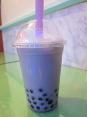 plastic cup of taro bubble tea, ie an opaque lavender liquid with dark globules of tapioca pearls visible at the bottom
