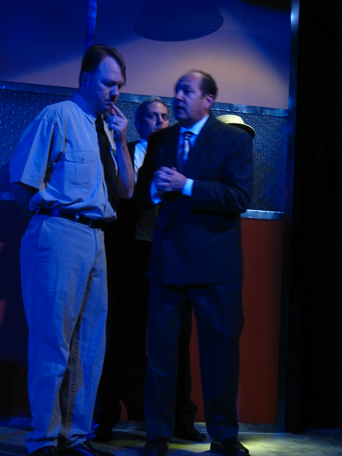 Hitler confers with a wealthy businessman (Bruno Oliver) while an American spy (Curt Bonnem) looks on.
