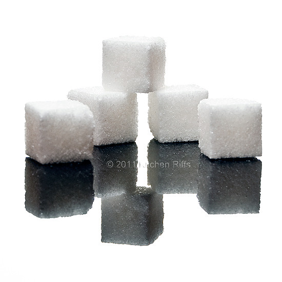 3 Sugar Cubes and reflections on black acrylic
