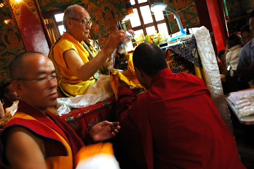 His Holiness Jigdal Dagchen Sakya accepting the body of the Buddha (Ku or statue) in a mandala of the universe offering by a Tibetan monk, with master of ceremonies assisting, Tharlam Monastery of Tibetan Buddhism, Boudha, Kathmandu, Nepal
