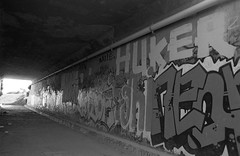 Secret you away (QsySue) Tags: blackandwhite slr graffiti pipe wideangle tunnel tags 35mmfilm roller orangecounty anaheim canonae1program floe batle neor huke developedathome 28mm128 35mmfilmcamera huker titleisadecemberistslyric orangecountyefke50