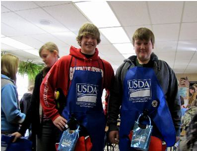 Huntsville Middle School 8th Graders, Colby Smith and Cody Levan, display the food safety gear given to them by FSIS employees.