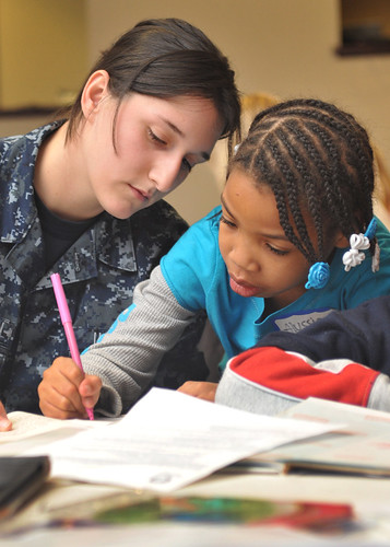 Sailor writes notes of encouragement with student.