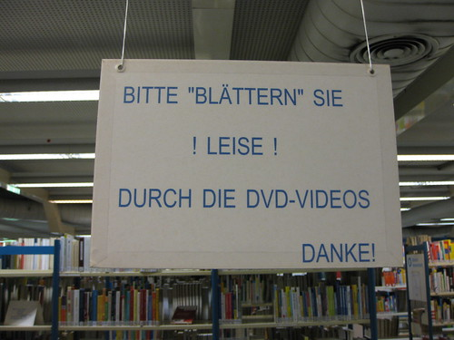 Photo Schild in einer Bibliothek mit Aufschrift 'Bitte blätern Sie leise durch die DVD-Videos'