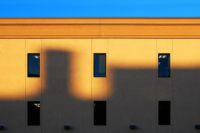 Shadows on a warm building, with a blue sky.