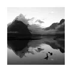 Milford Sound (Monochrome Visions) Tags: morning newzealand sky mountains water monochrome clouds reflections square mono blackwhite peak sound southisland fjord milfordsound blackdiamond canoneos1000d dexodexo douwedijkstra