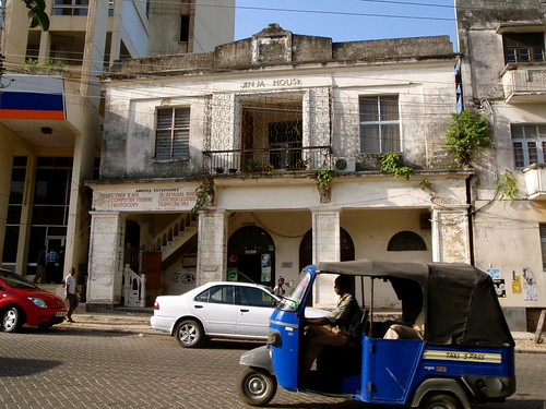 Two-storey colonial building on cobbled street; three wheeled tuk-tuk in foreground