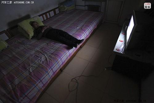 3月26日晚,河北沧州泊头货场,郭伟明独自一人在通铺上看电视等待装货。郭伟明,42岁,黑龙江黑河人,2009年在客运公司卖票下岗后,通过亲戚担保贷款8万元买了辆大货车,和妻子一起开始跑河北泊头和哈尔滨之间1400公里的专线。