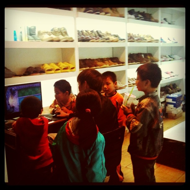 Fieldwork: neighborhood kids crowded around store owner playing games on computer